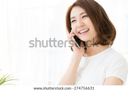 Beautiful young asian woman who talks on the telephone - stock photo