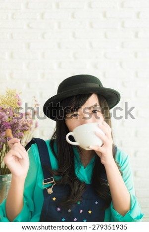Beautiful young asian woman with a cup of tea at a cafe, White brick wall background - stock photo