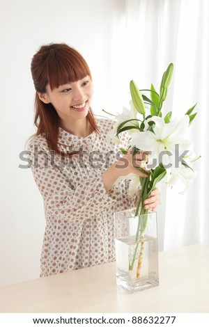 Beautiful young Asian woman with flowers - stock photo