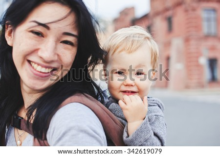 Beautiful young asian woman with freckles and her son on walk. Mother brunette with dark hair and her son is blond. Unusual appearance and heredity concept. Baby sits in sling on mothers back - stock photo