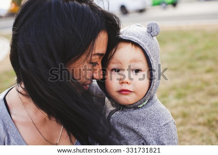 Beautiful young asian woman with freckles and her son outdoors. Mother brunette with dark hair holds her blond son in bear hood. Emotions on baby face. Unusual appearance, diversity, heredity concept - stock photo