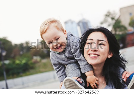 Beautiful young asian woman with freckles and her son outdoors. Mother brunette with dark hair and ear piercing and her son is blond. Unusual appearance and heredity concept. Son sits on mother's neck - stock photo