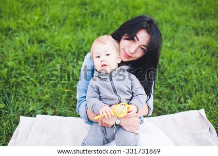 Beautiful young asian woman with freckles and her son sit on grass at picnic. Mother brunette with dark hair and her son is blond. Unusual appearance, diversity and heredity concept. Copy space  - stock photo