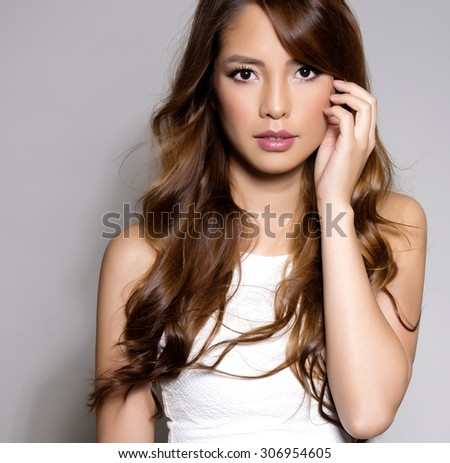 beautiful young asian woman with long hair, flawless skin and perfect make-up - stock photo
