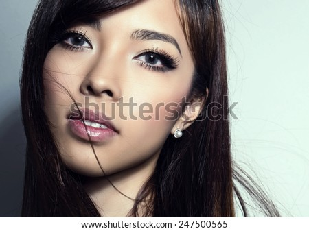 beautiful young asian woman with perfect skin posing in a close up picture with flawless make-up, lipstick, mascara and eye-shadows - stock photo