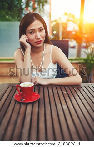 Beautiful young asian woman with red lips sitting in cafe terrace exterior with amazing sunset on background, portrait of gorgeous female enjoying a delicious coffee at restaurant in summer sunny day