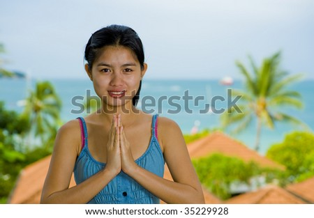 beautiful young asian woman with welcome expression in front of the sea - stock photo
