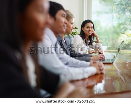Beautiful young asian woman working and smiling at camera during business meeting with colleagues. - stock photo