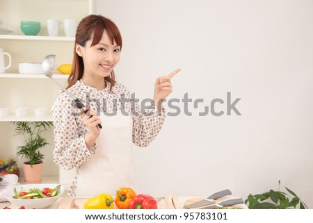 Beautiful young Asian women point to the text space in the kitchen - stock photo