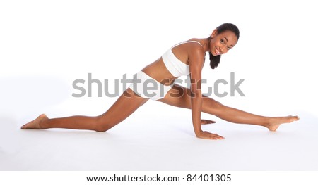 Beautiful young athletic African American fitness woman wearing sports underwear, having fun doing warm up leg stretch on the floor with big happy smile. - stock photo