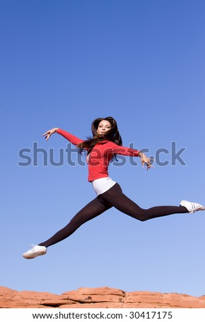 Beautiful young athletic woman jumping high