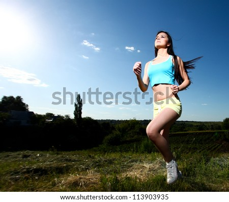 Beautiful young athletic woman running through the green grass against the blue sky - stock photo
