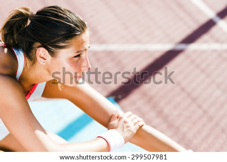 Beautiful young athletic woman stretching in summer before running