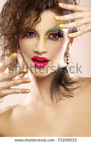 Beautiful young attractive female face with bright fashion multicolored make-up and beauty yellow manicure of fingernails