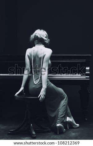 Beautiful young attractive woman in cocktail dress and piano