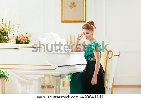 Beautiful young attractive woman in dress playing white piano - stock photo