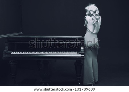 beautiful young attractive woman in evening dress and piano (black and white shoot) - stock photo
