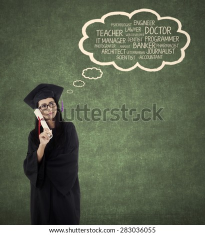 Beautiful young bachelor imagine her future jobs after finishing her study while wearing graduation gown - stock photo
