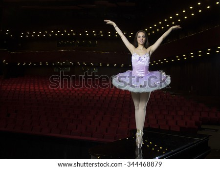 Beautiful young ballerina posing on piano. Large theater house behind. - stock photo