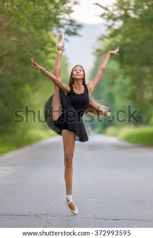 Beautiful young ballerina posing outdoor. Gymnast girl doing exercise in nature - stock photo