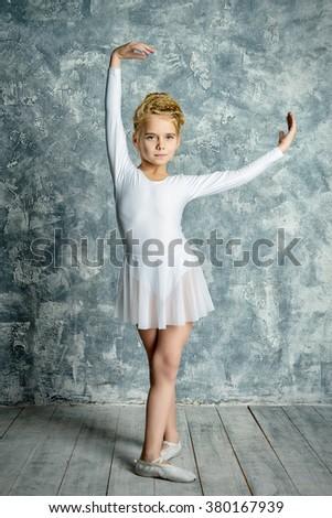 Beautiful young ballet dancer posing in studio. - stock photo