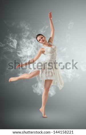 Beautiful young ballet dancer with smoke curles around her - stock photo
