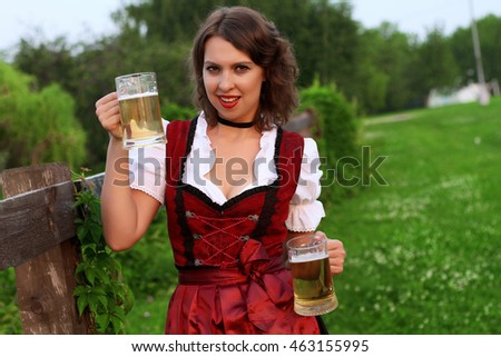 Beautiful, young, Bavarian woman in dirndl holding oktoberfest rose. Close-up