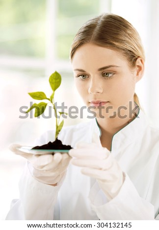 Beautiful young biologist experimenting in laboratory. Woman studying green sprout - stock photo