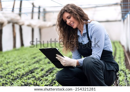 Beautiful young biotechnology woman engineer with clipboard and pen, examining plants for disease in greenhouse with apron and gloves. Greenhouse produce. Food production. - stock photo