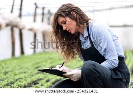Beautiful young biotechnology woman engineer with clipboard and pen, writing and examining plants for disease in greenhouse with apron and gloves. Greenhouse produce. Food production. - stock photo