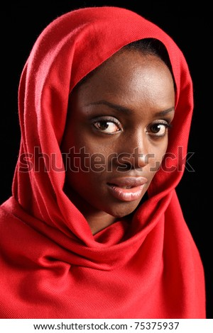 Beautiful young black african muslim woman wearing red headscarf, taken against a black background. - stock photo