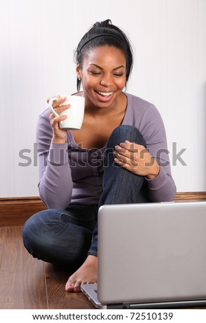 Beautiful young black student girl, big smile, sitting on the floor at home, using her laptop to communicate with friends. - stock photo