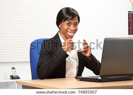 Beautiful young black woman enjoying her coffee while working in the office. - stock photo