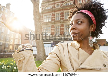 Beautiful young black woman holding the sun between her fingers at sunset while visiting London city.