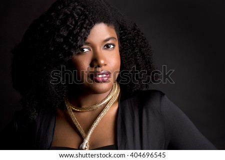 beautiful young black woman is wearing dark dress on grey background - stock photo