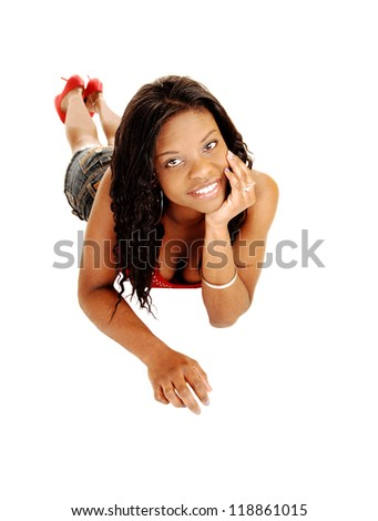 Beautiful young black woman lying on her stomach for white background resting her head on her hand and smiling into the camera.