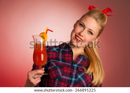beautiful young blond caucasian  pinup woman with a glass of cocktail - stock photo