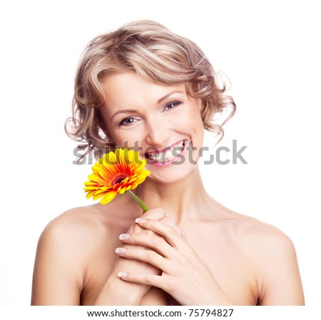 beautiful young blond curly woman with a flower in her hands - stock photo