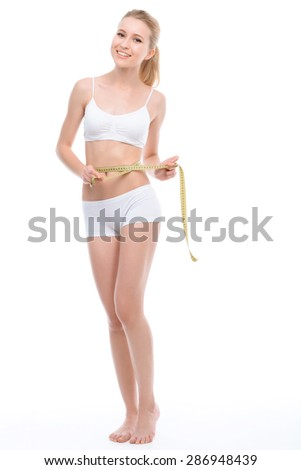 Beautiful young blond fit girl wearing white bra and panties standing smiling holding a measure tape on her waistline, isolated on a white background, full length - stock photo