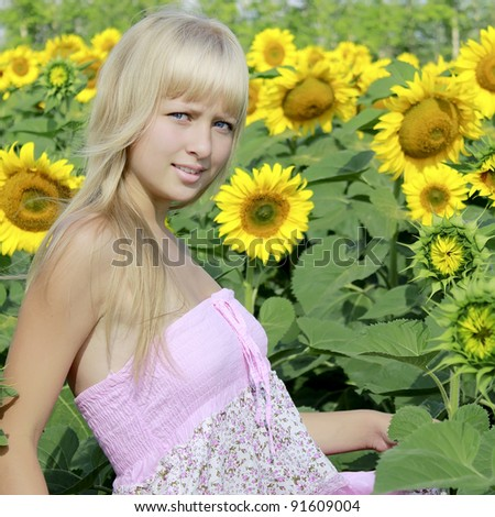 Beautiful young  blond girl among sunflower in summer - stock photo