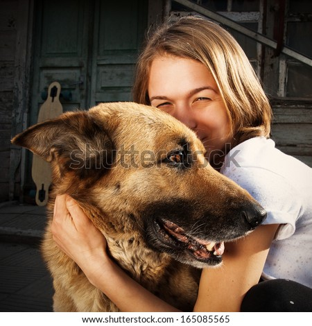 beautiful young blond girl hugging with love a big dog