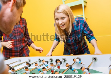 Beautiful young blond girl looking challenging at her partner while playing air hockey, her friend cheering her up in a yellow room - stock photo