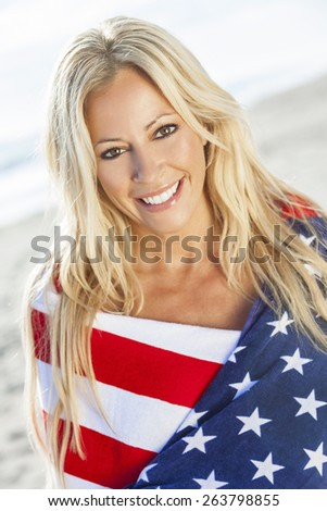 Beautiful young blond girl or young woman smiling wearing bikini and wrapped in American flag towel on a sunny beach - stock photo