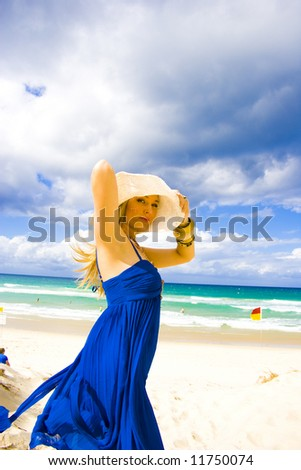 beautiful young blond girl standing on the beach in a blue dress
