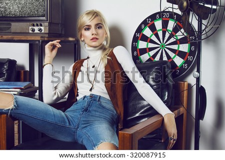 Beautiful young blond girl wearing cowboy clothes and posing like a doll. She is captured in nice scene with old TV, phone, furniture, magazines, table, pictures, dartboard and fen.  - stock photo
