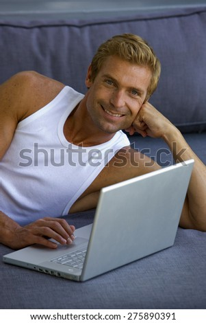 Beautiful young blond man lying down on blue sofa and using laptop.  - stock photo