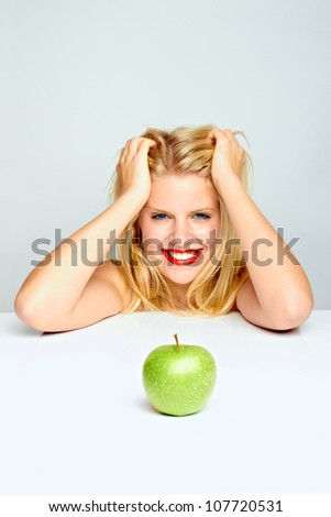 beautiful young blond smiling girl with green apple - stock photo