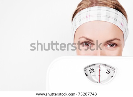 beautiful young blond sporty woman  holding scales, copy space for your text to the left - stock photo