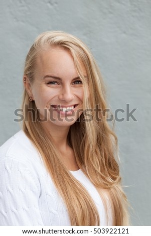 Beautiful, young, blond, Swedish woman looking happy with a smile on her lips.