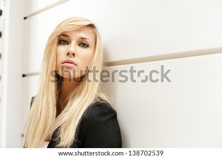 Beautiful young blond wearing black formal uniform leaning on the white wall. Look in to the camera - stock photo